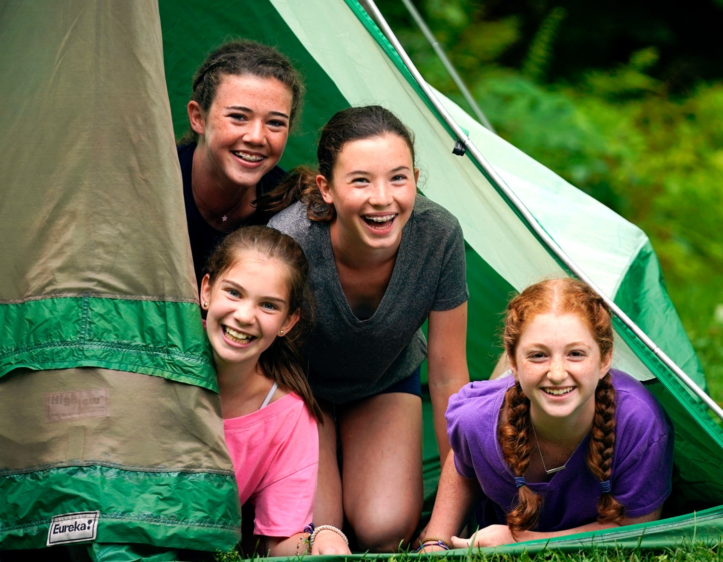 four girls peaking out of a green tent smiling