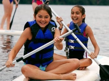 two girl smiling and sitting on a paddle board
