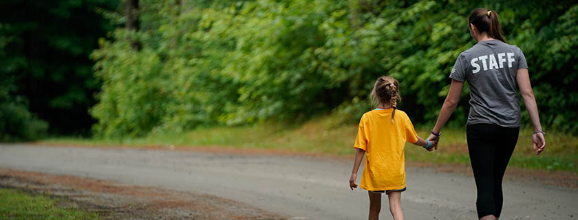 camper and counselor holding hands while walking down a road