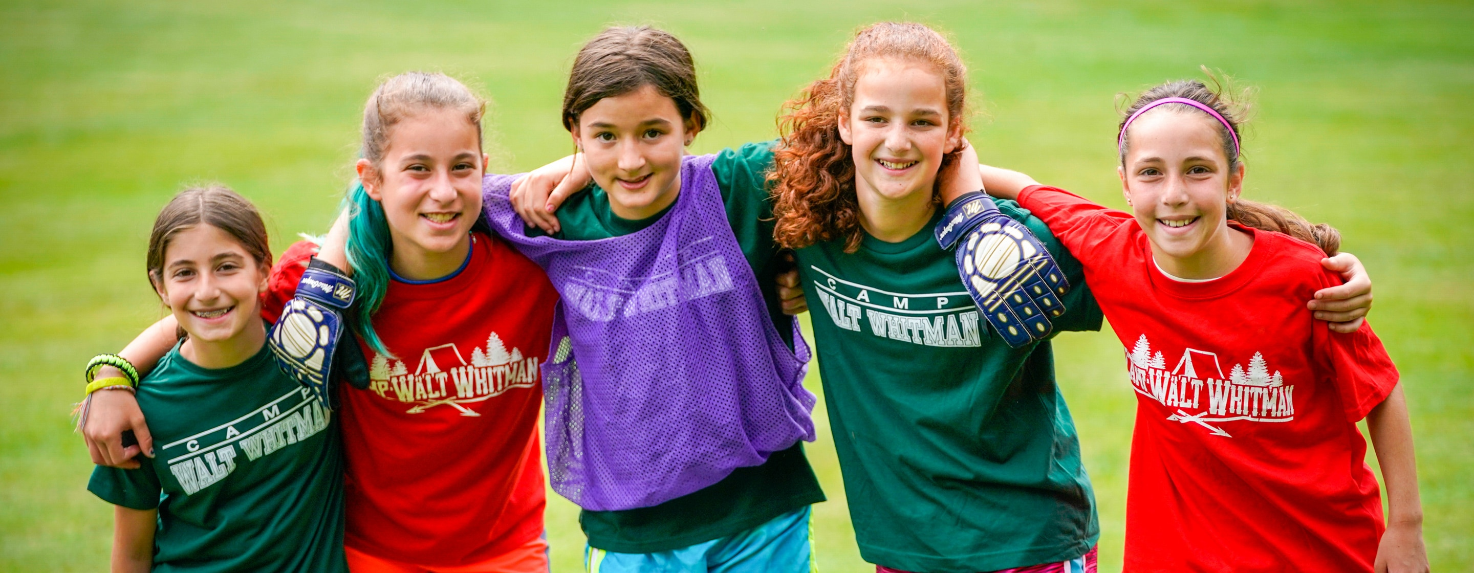young girls with soccer gear holding shoulders