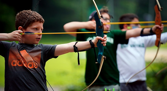 three youngs boys shooting a bow and arrow