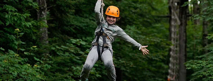 camper smiling while ziplining