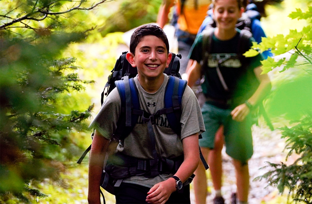 boy smiling while he's hiking in the woods