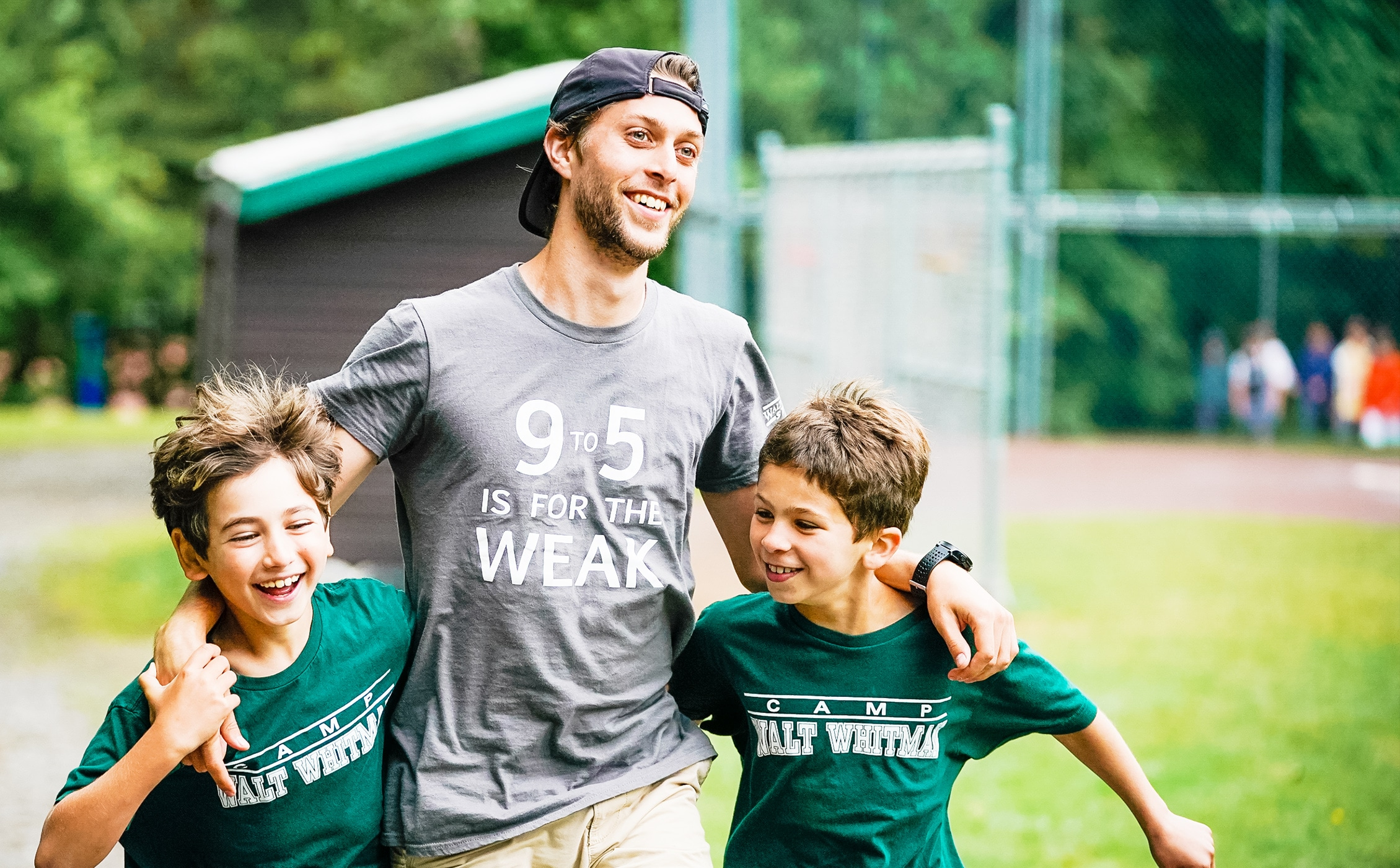 a camp counselor holding two young boys around their shoulder