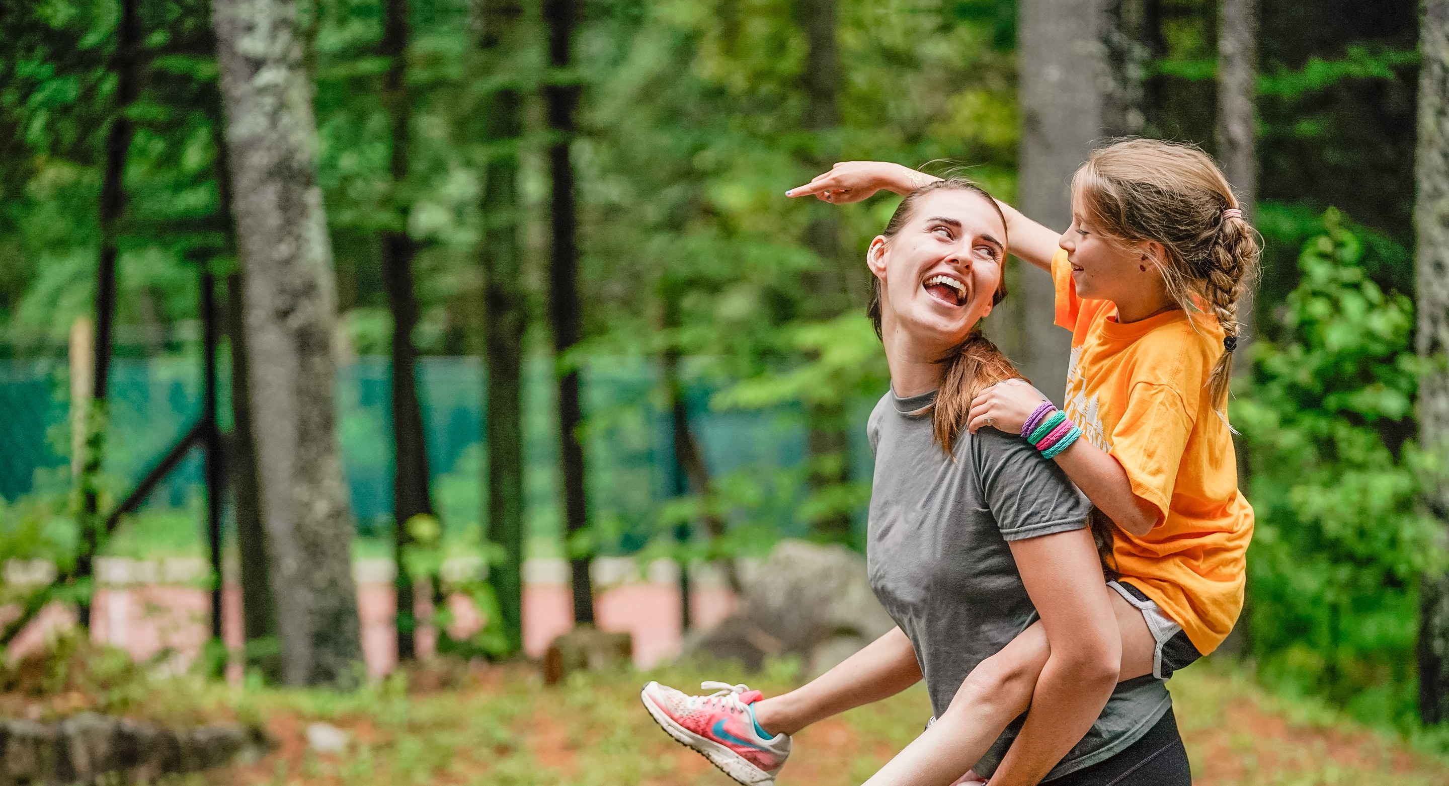 camp counselor looking back and smiling while giving a young girl a piggy back ride