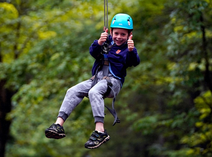 camper giving two thumbs up while they zipline