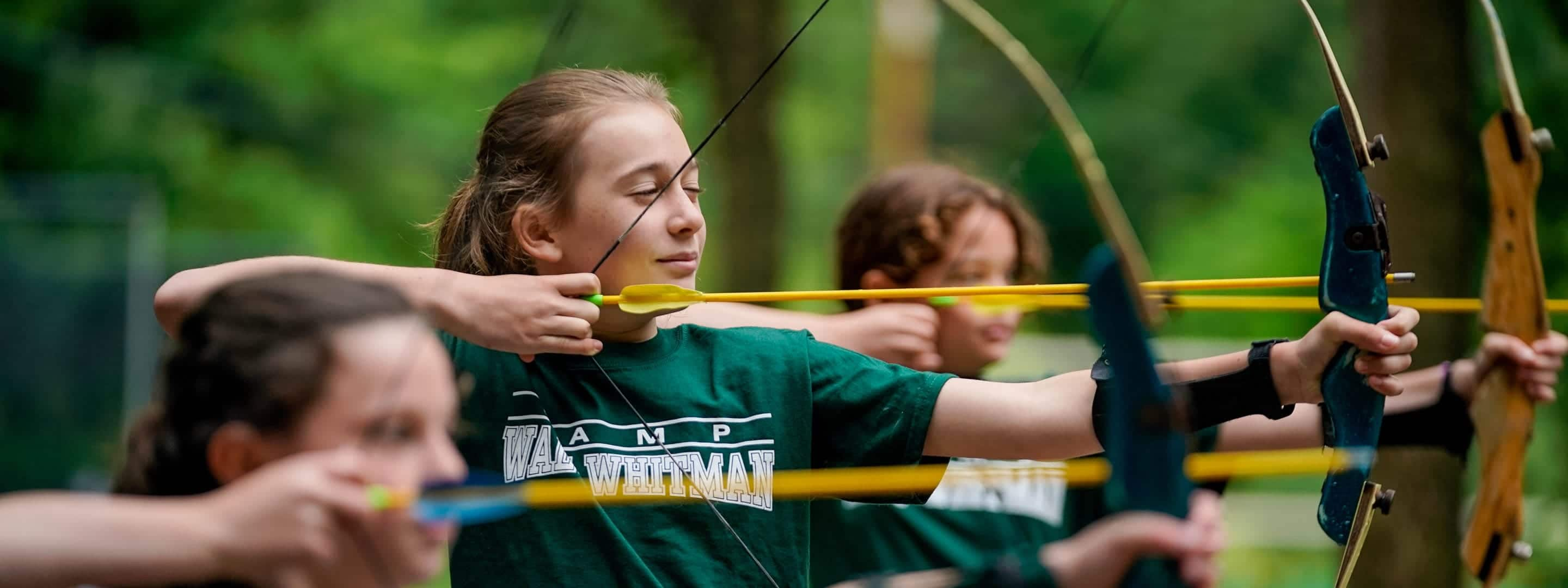 girls shooting a bow and arrow