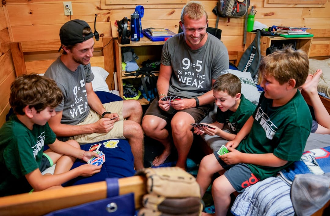 campers and counselors on beds playing a card game