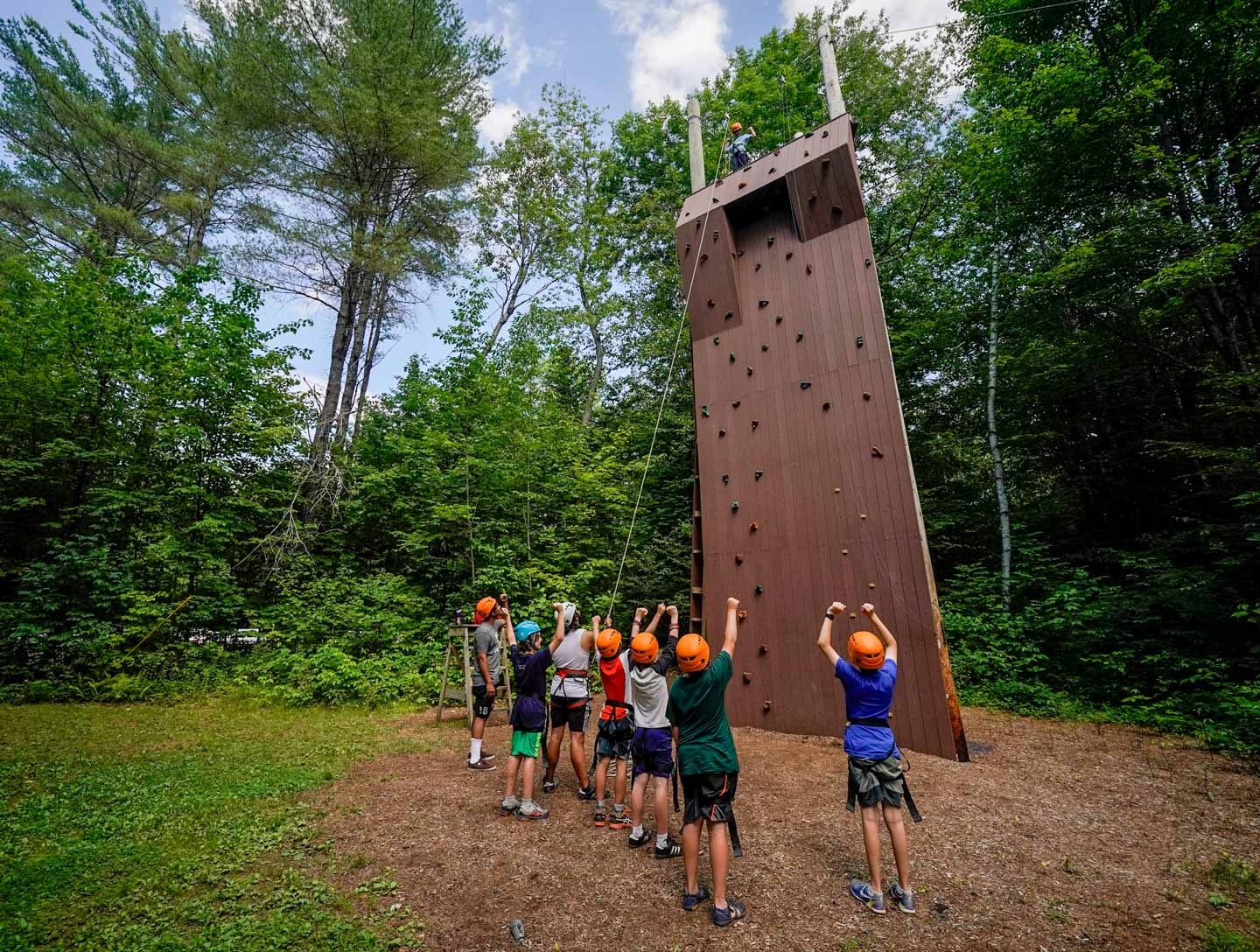 camper at top of rock climbing wall while a group at the bottom celebrate