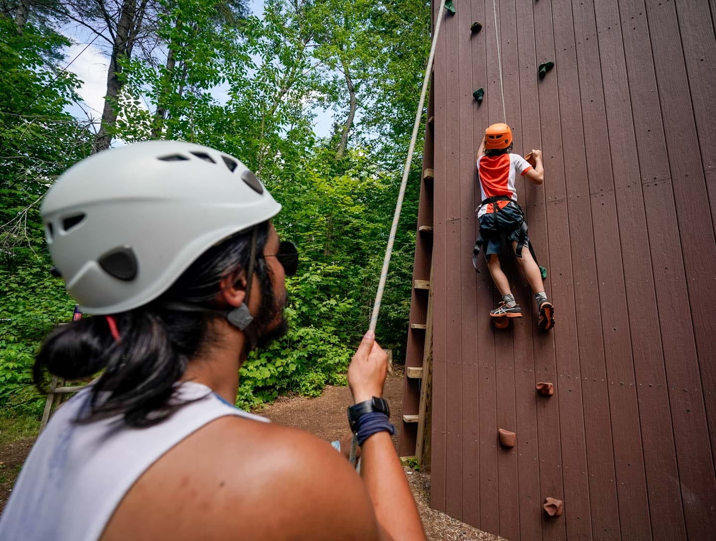 a camper climbing a rock wall while an instructor belays him