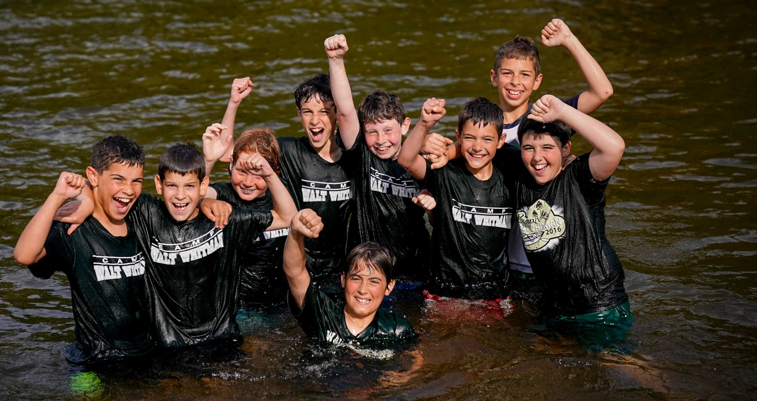 young boys cheering while in water