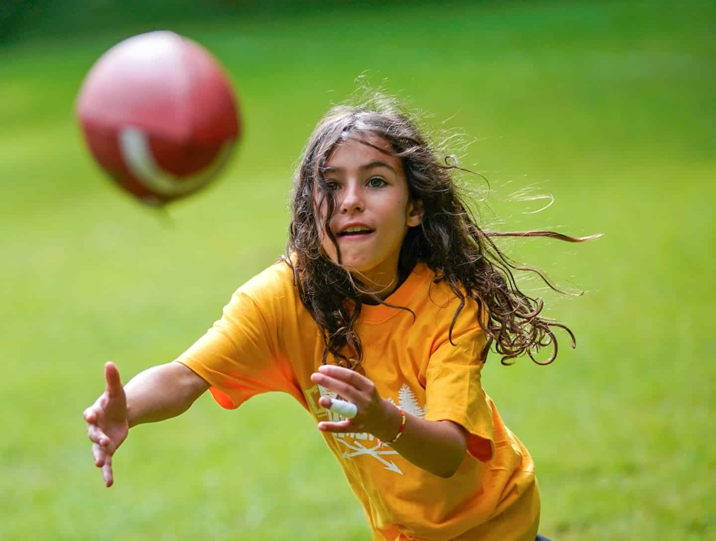 young girl about to catch a football