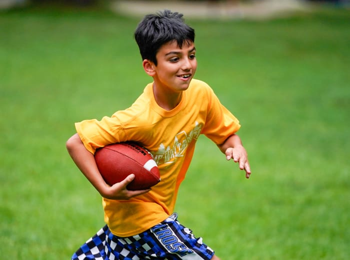 young boy running with a football