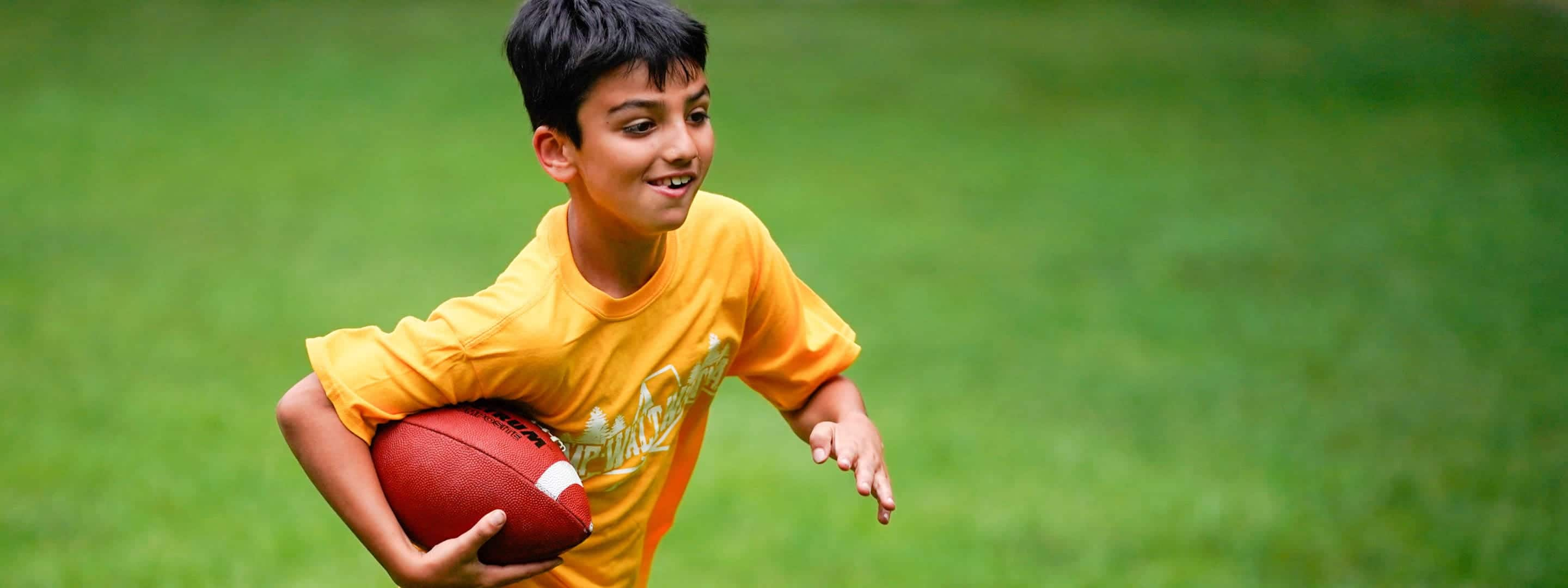 boy running with a football