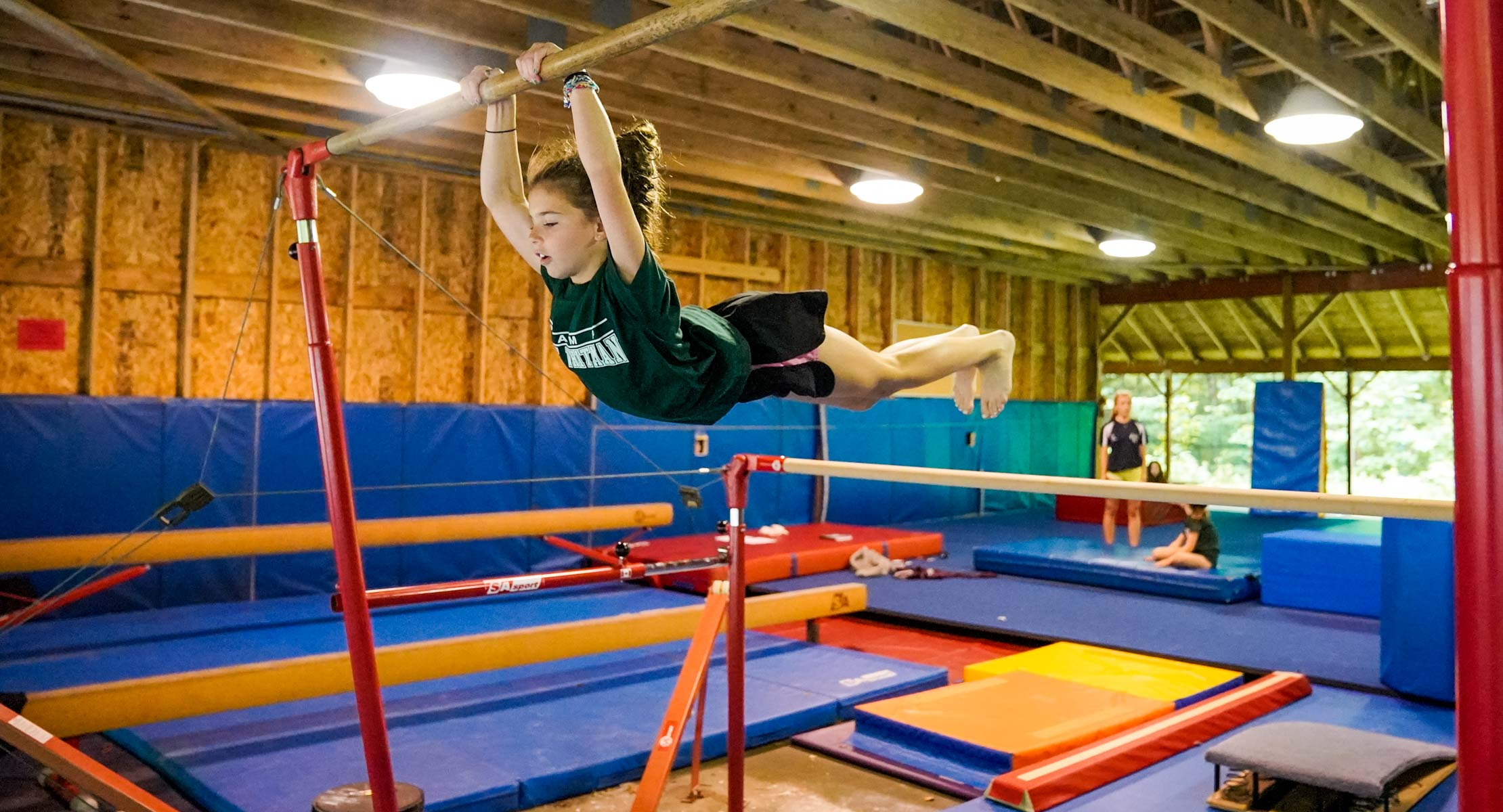 young girl swinging on the uneven bars