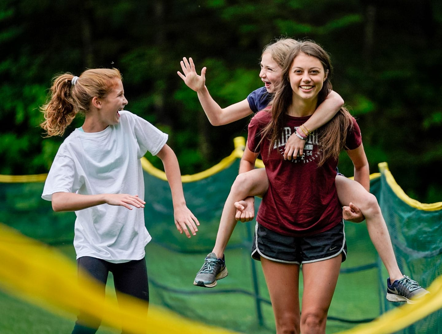 pretty camp counselor giving kid a piggy back ride while they high five another girl