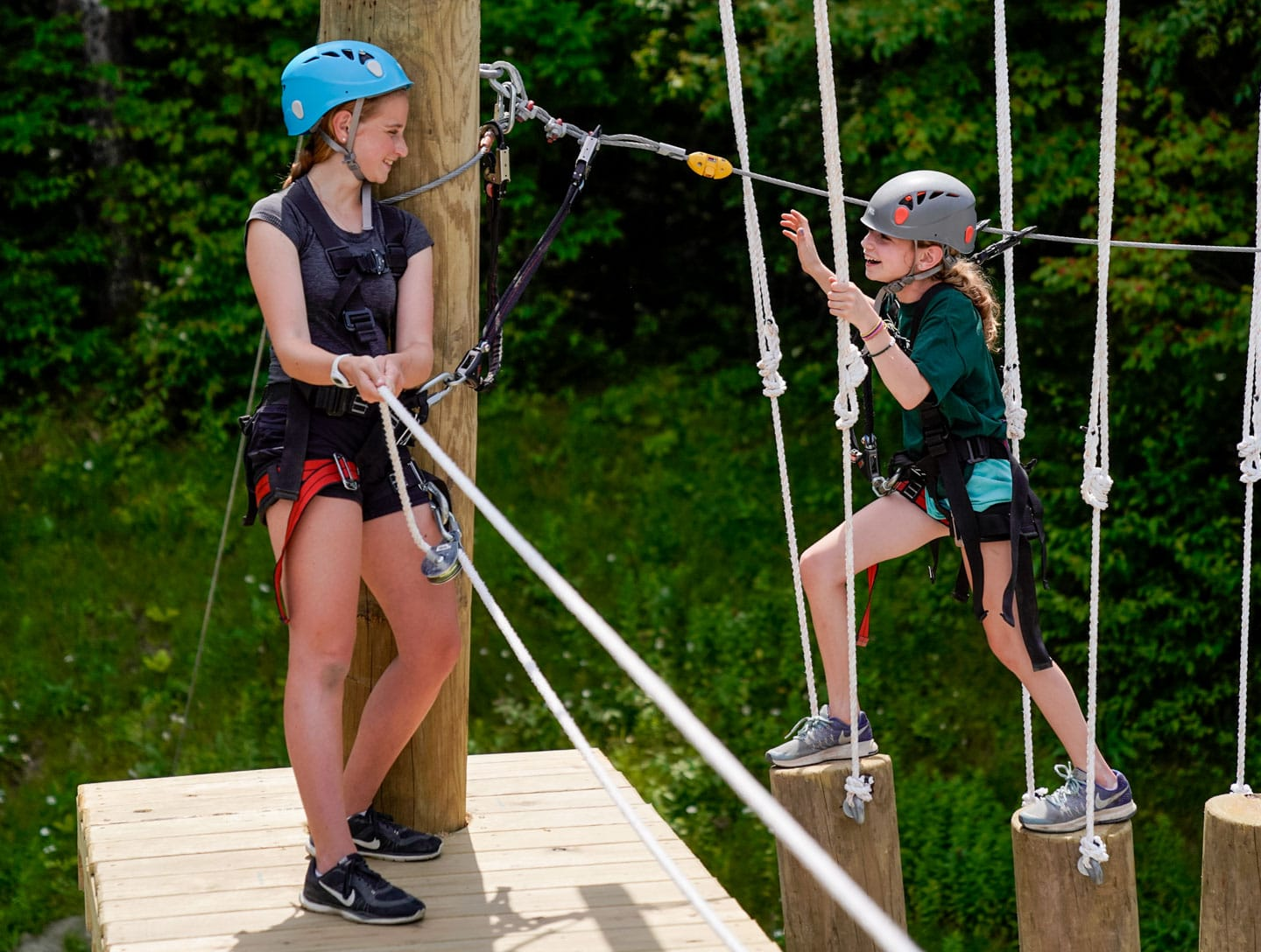 two girl climbing an aerial structure