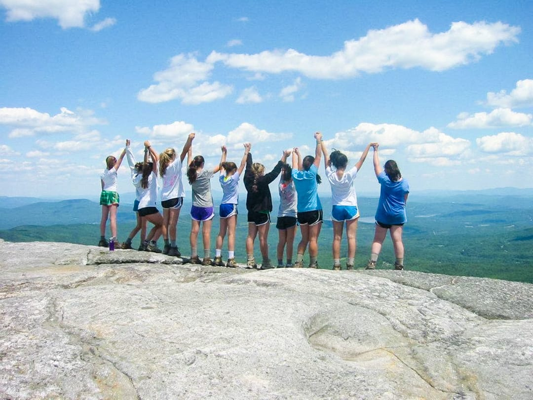 group of girls on the edge of a rock with their hands up