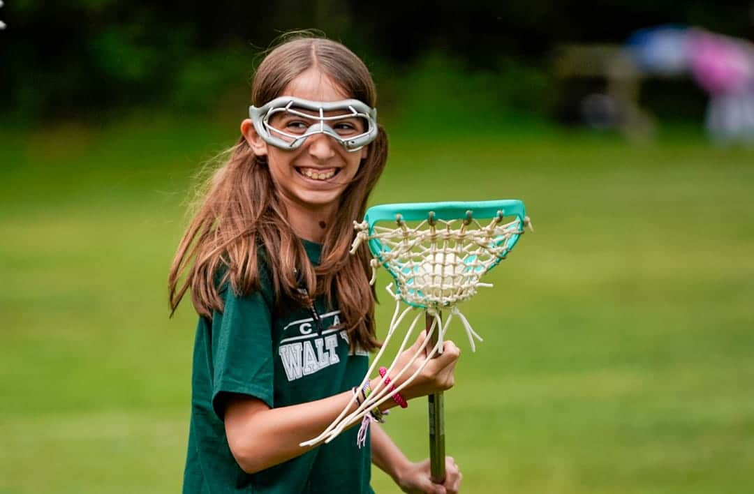 a young girl smiling while playing lacrosse