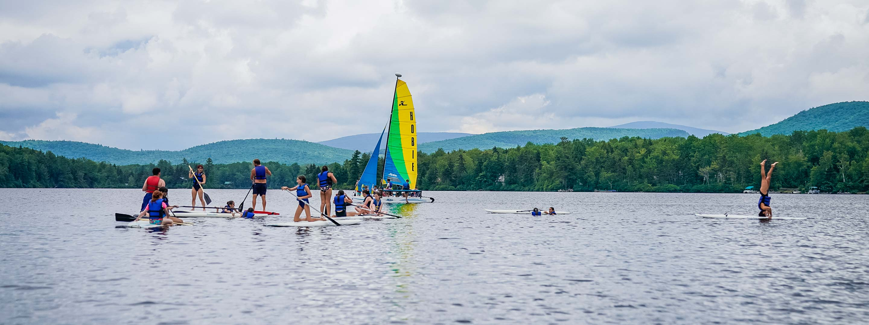 campers on sailboats and standing paddle boats on a lake