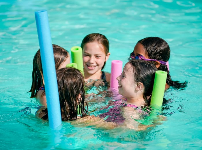 young girls in a pool with floaties