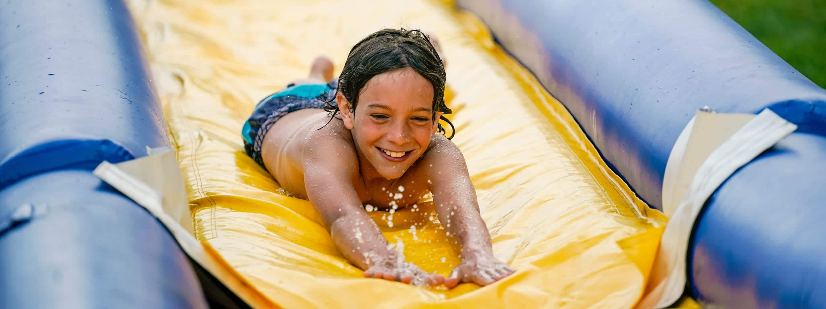 young kid sliding on a slip and slide