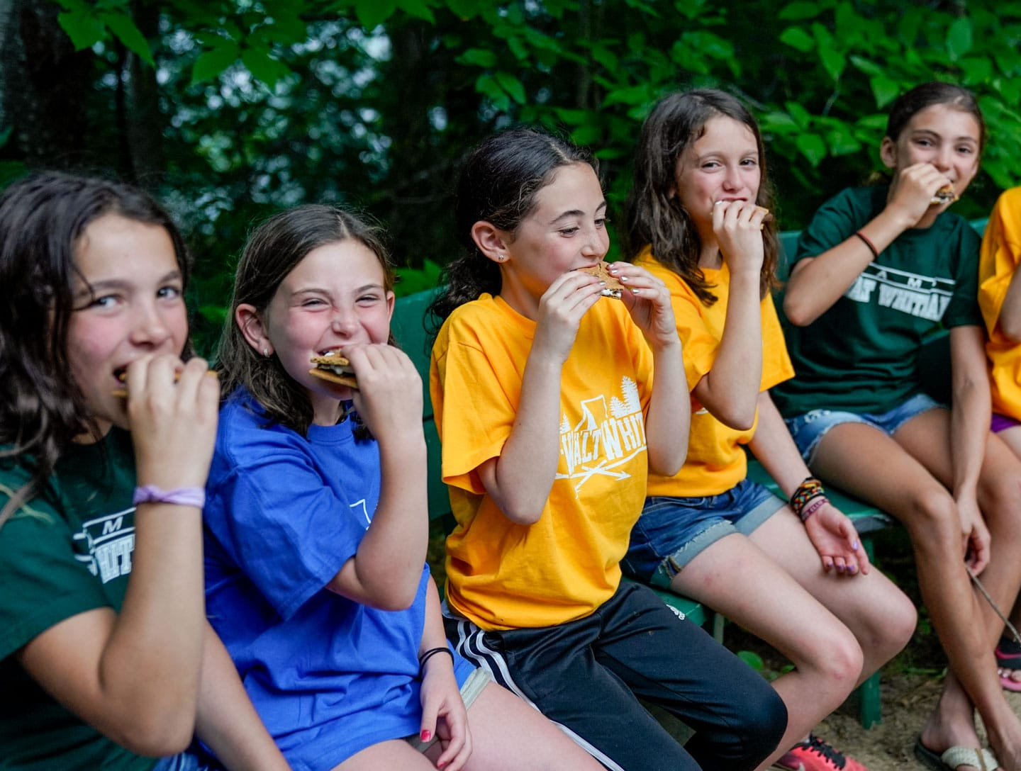 young girl campers eating smores