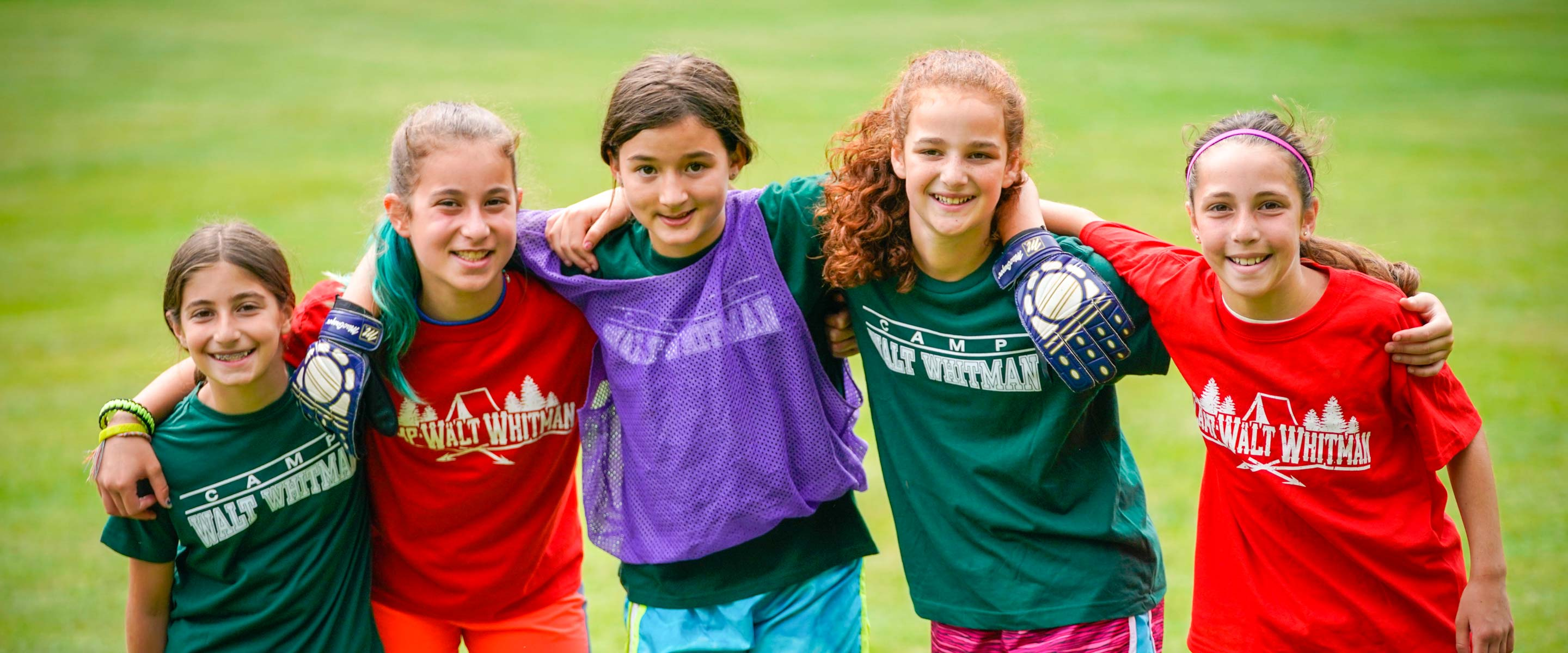 five young girls with arms around each other with soccer gear on