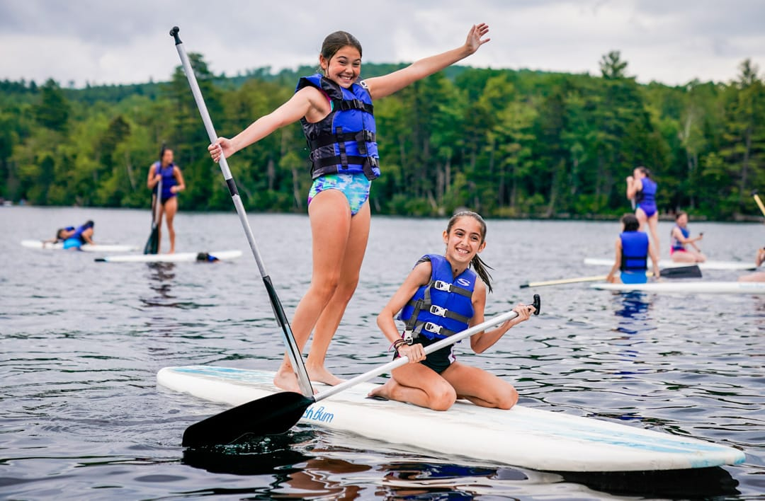 two young girls smiling on a standing paddle boat