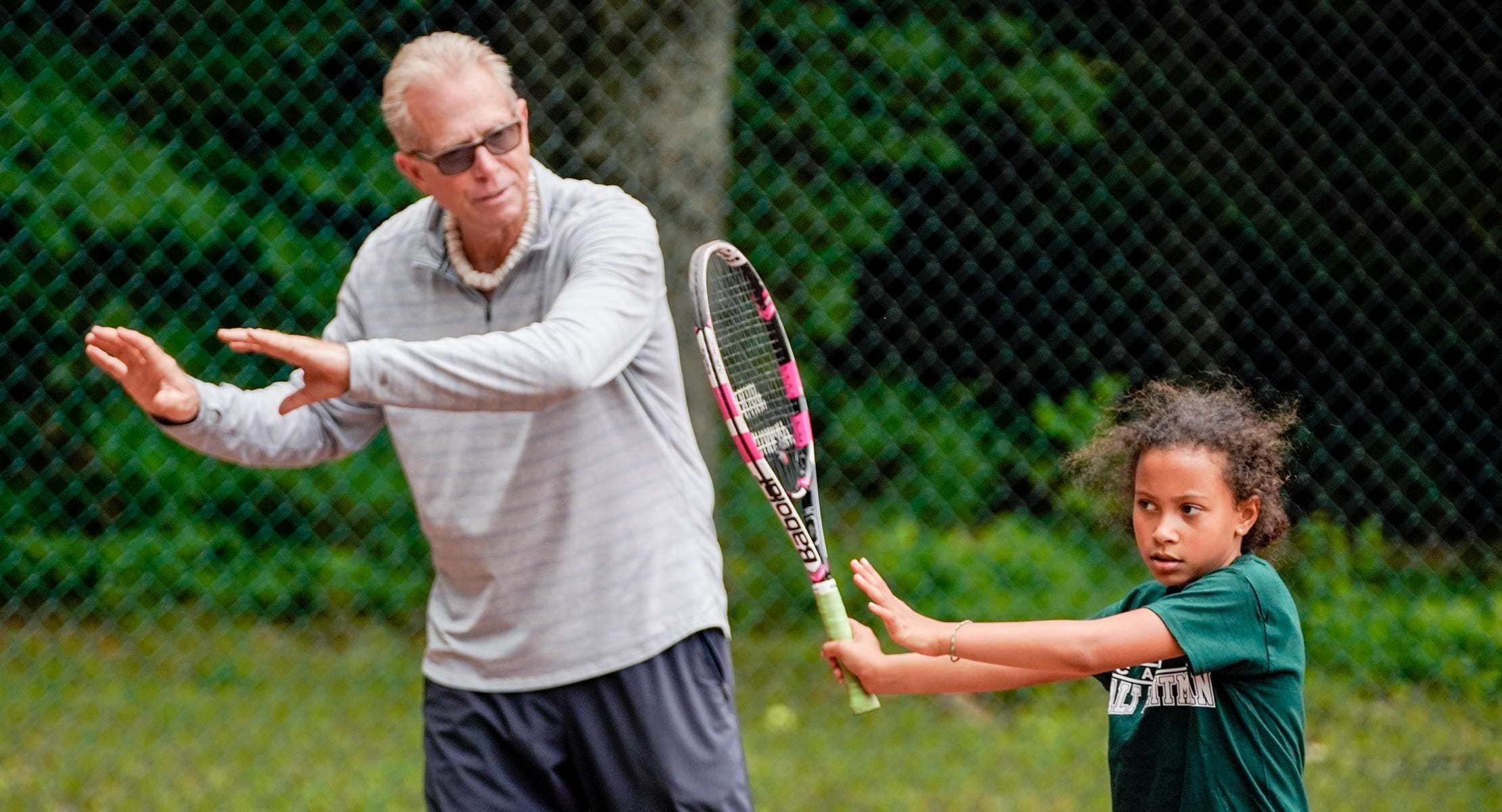 man demonstrating how to swing a tennis racket to young camper