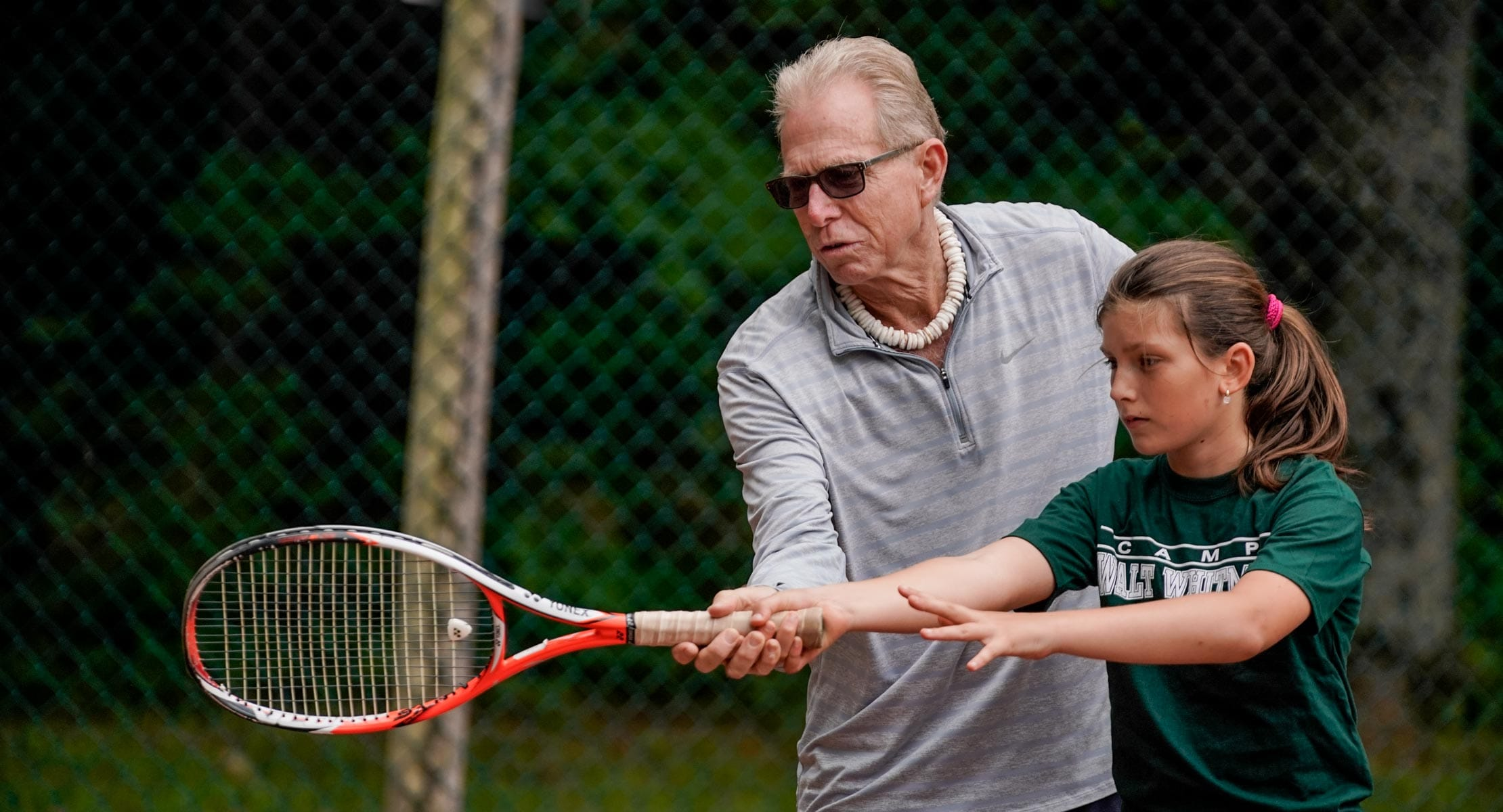 man showing young girl how to swing tennis racket