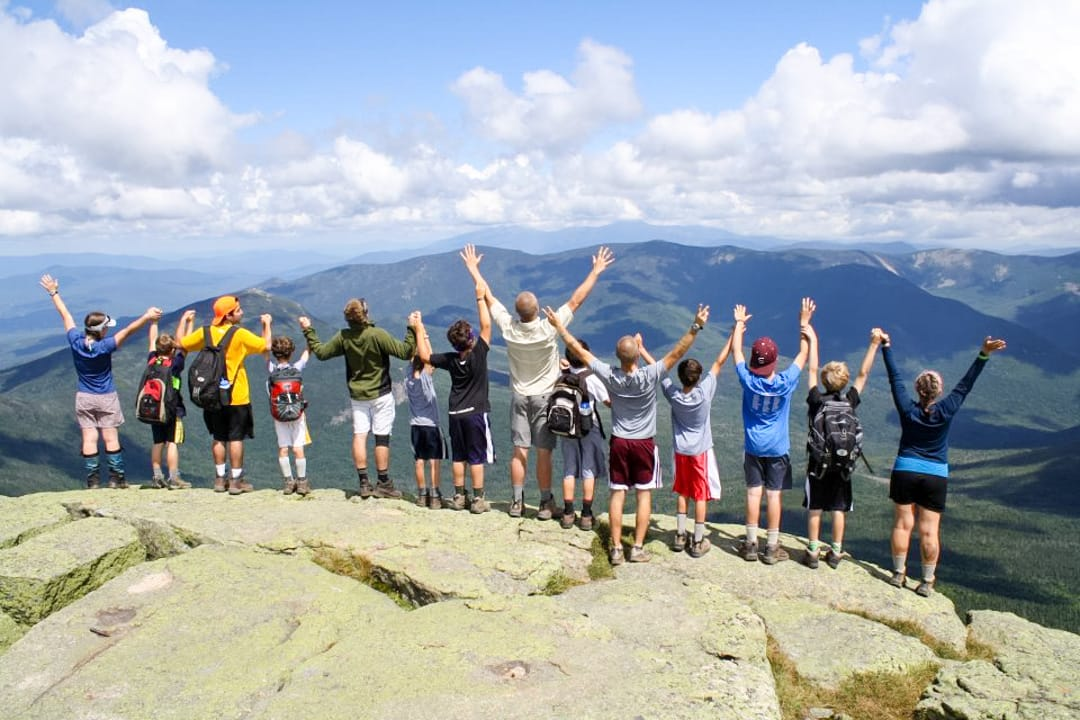 group of boys on the edge of a cliff rock with their hands up