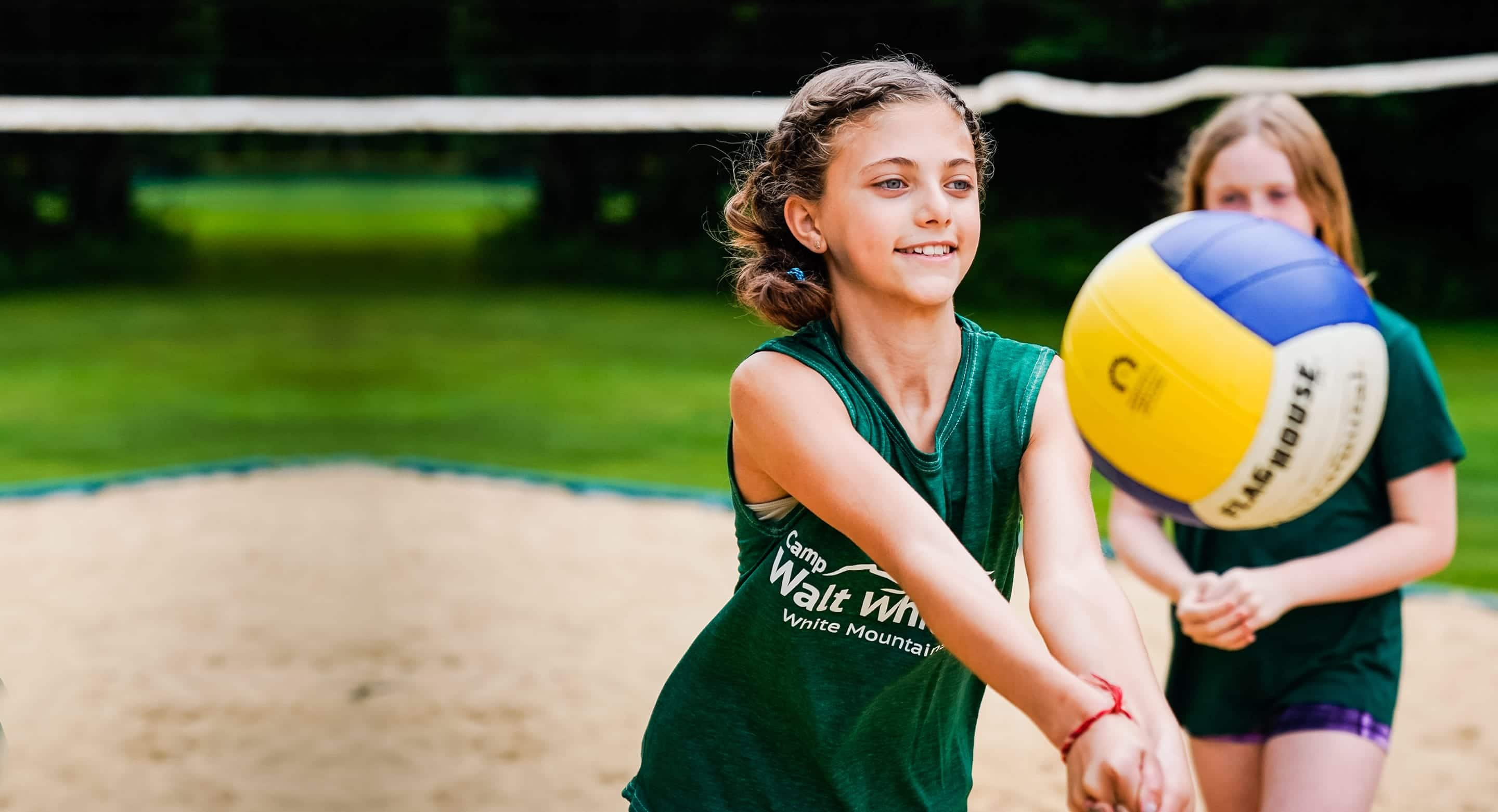 young girl smiling while passing an outdoor volleyball