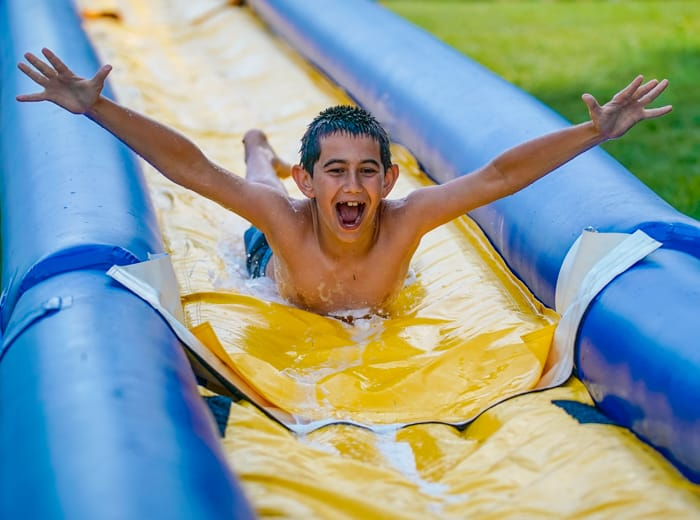 young boy on a slip and slide