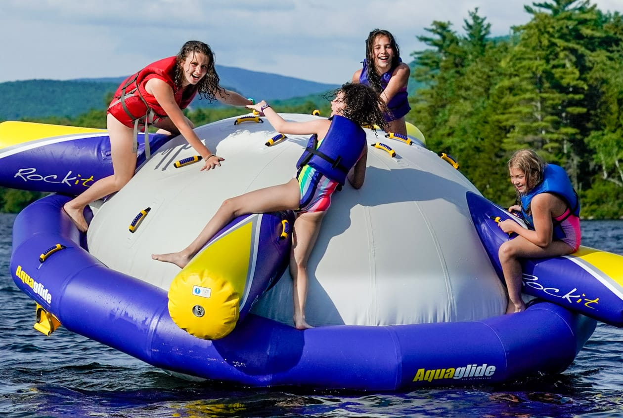 four girls clinging onto a wibit on a lake