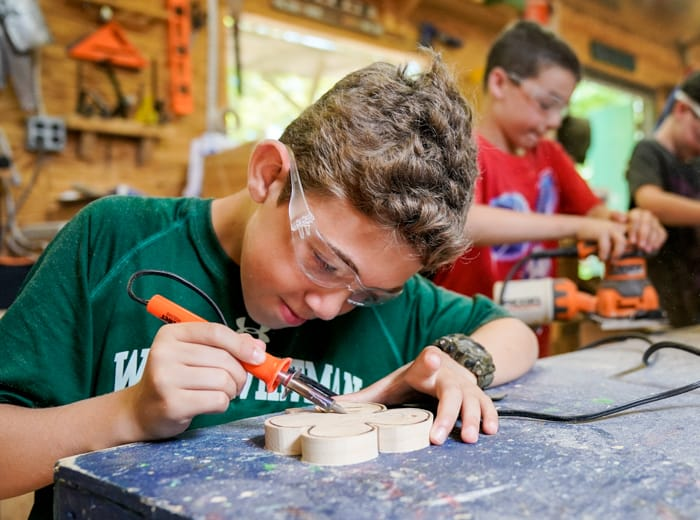 young boy soldering a four leaf clover in woodworking