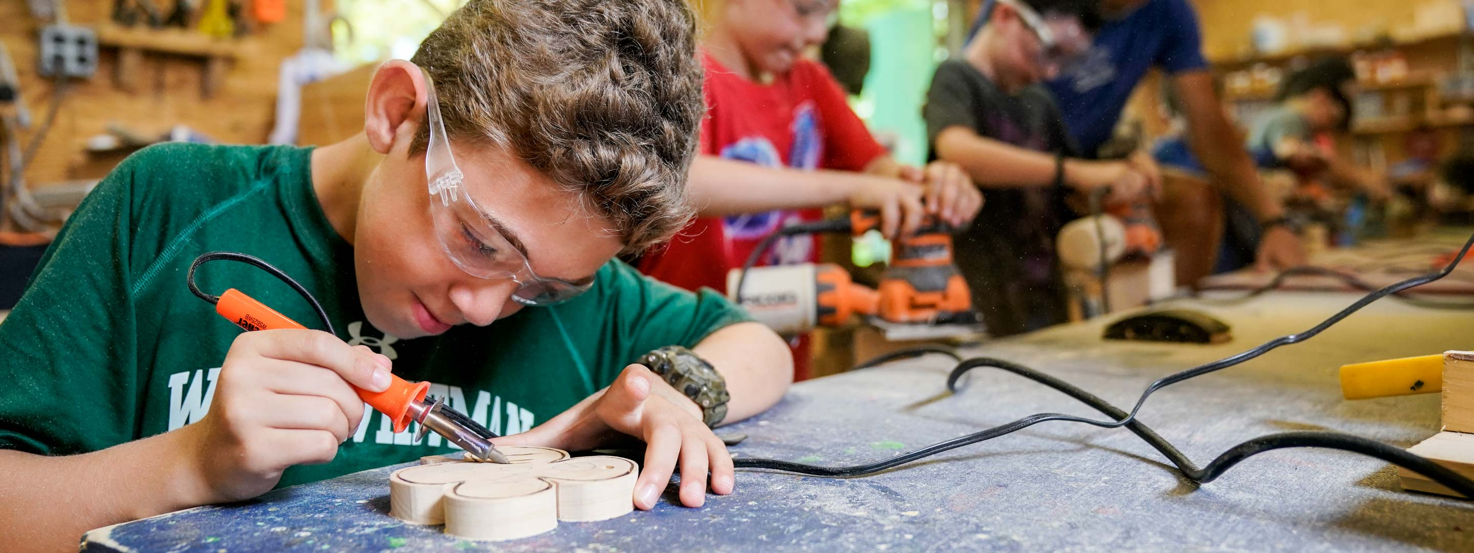 young boy with a soldering iron creating a four leaf clover design