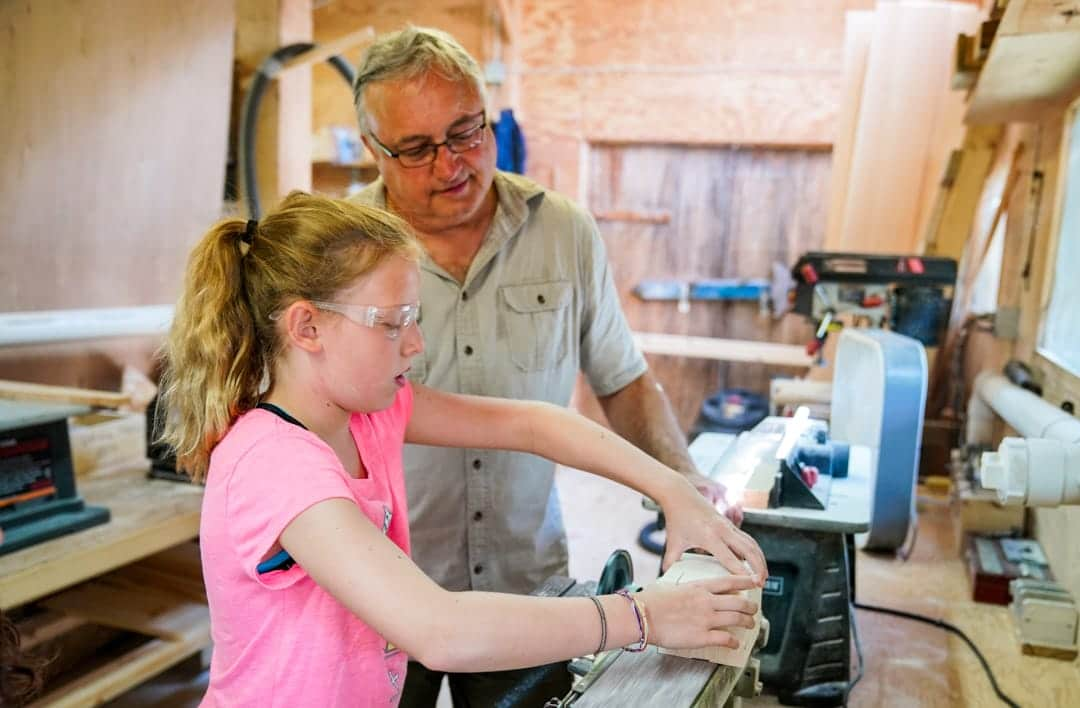 young girl wood working while an old man looks over her shoulder