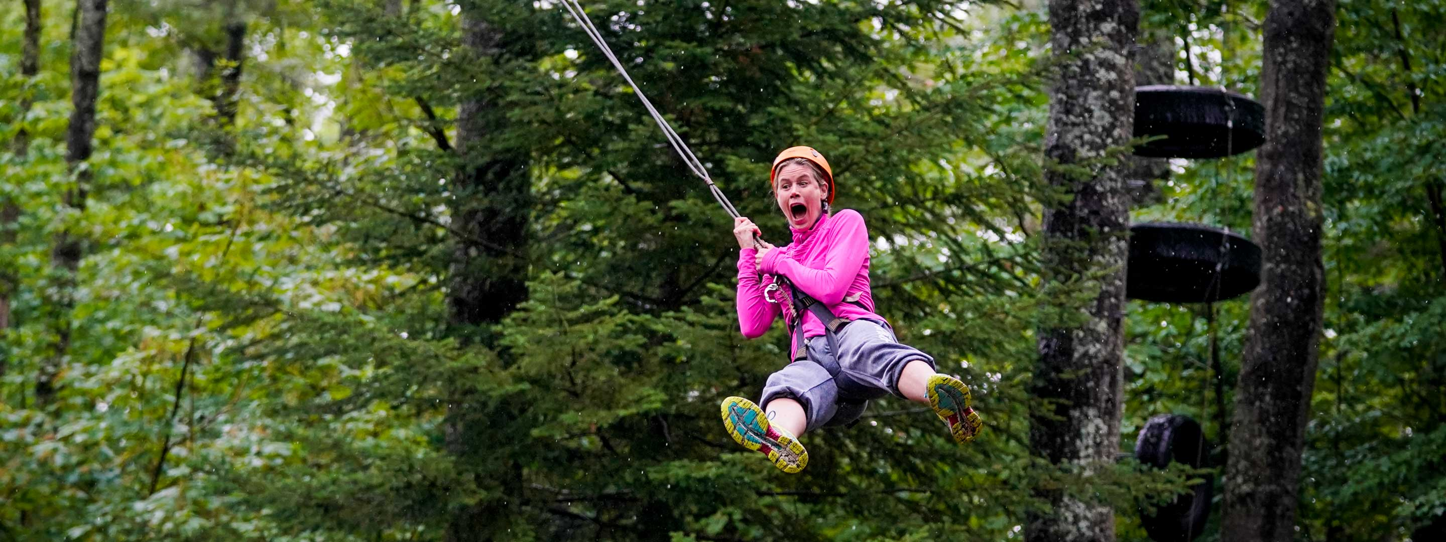 woman with a fearful look on her face on a zipline