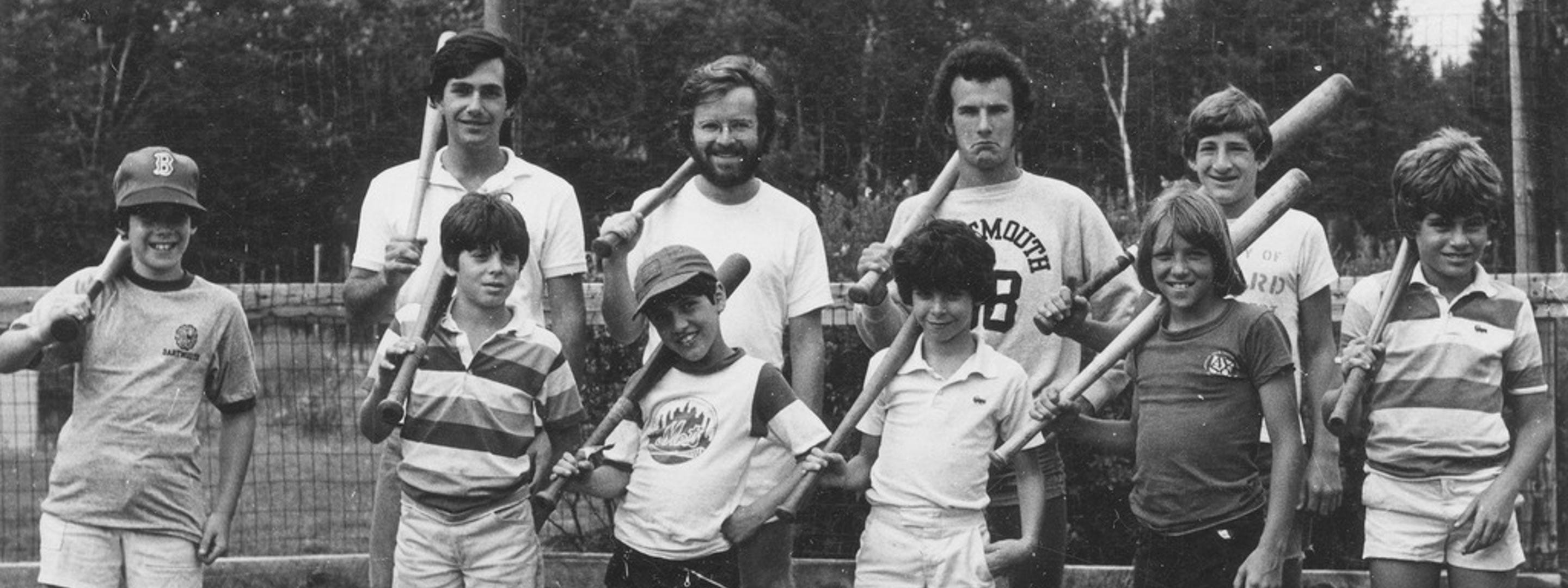 black and white picture of boy campers and counselors with baseball bats over their shoulders
