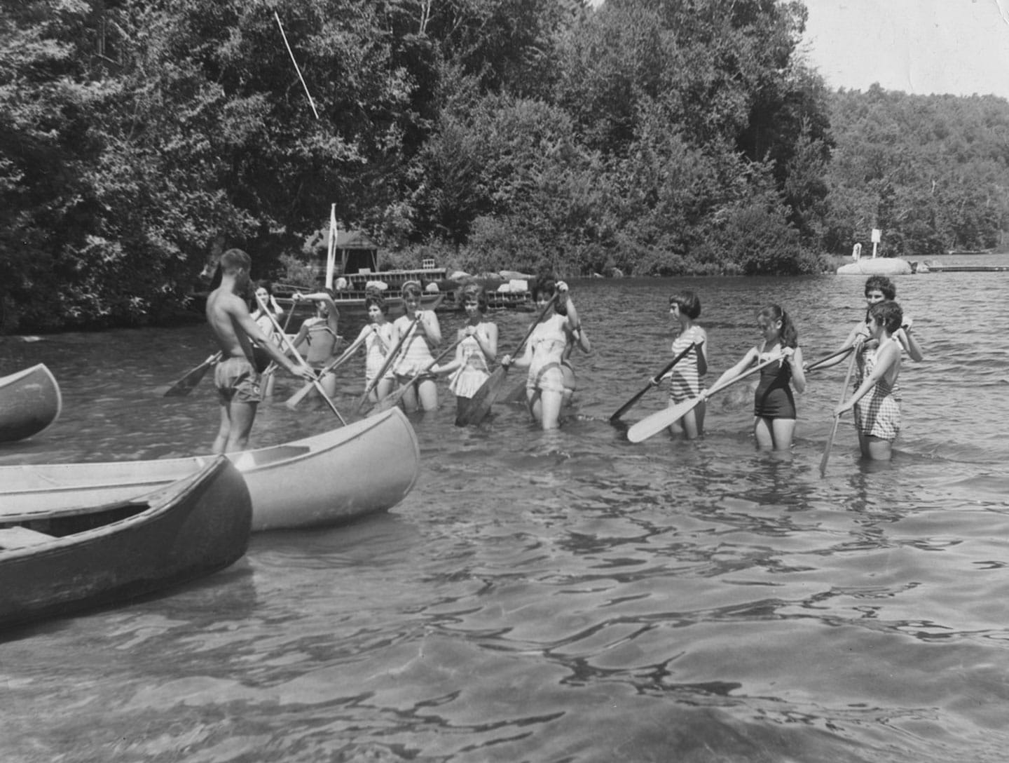 black and white picture of young woman standing in knee deep water learning how to paddle