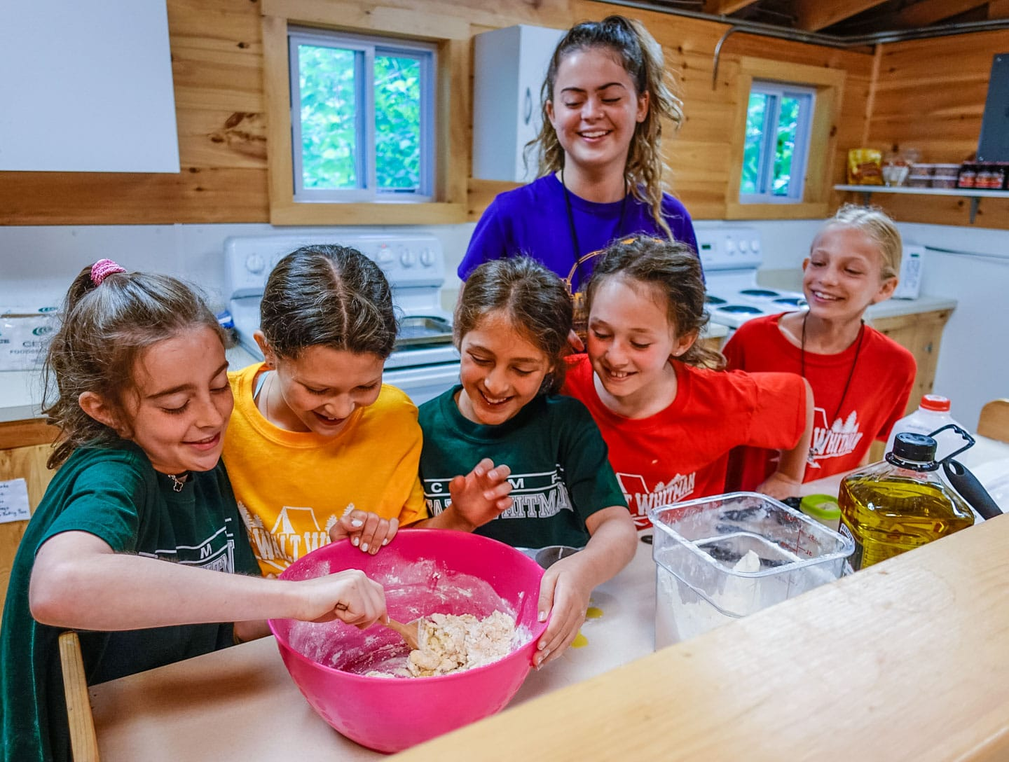 a group of girls helping mix ingredients in a bowl