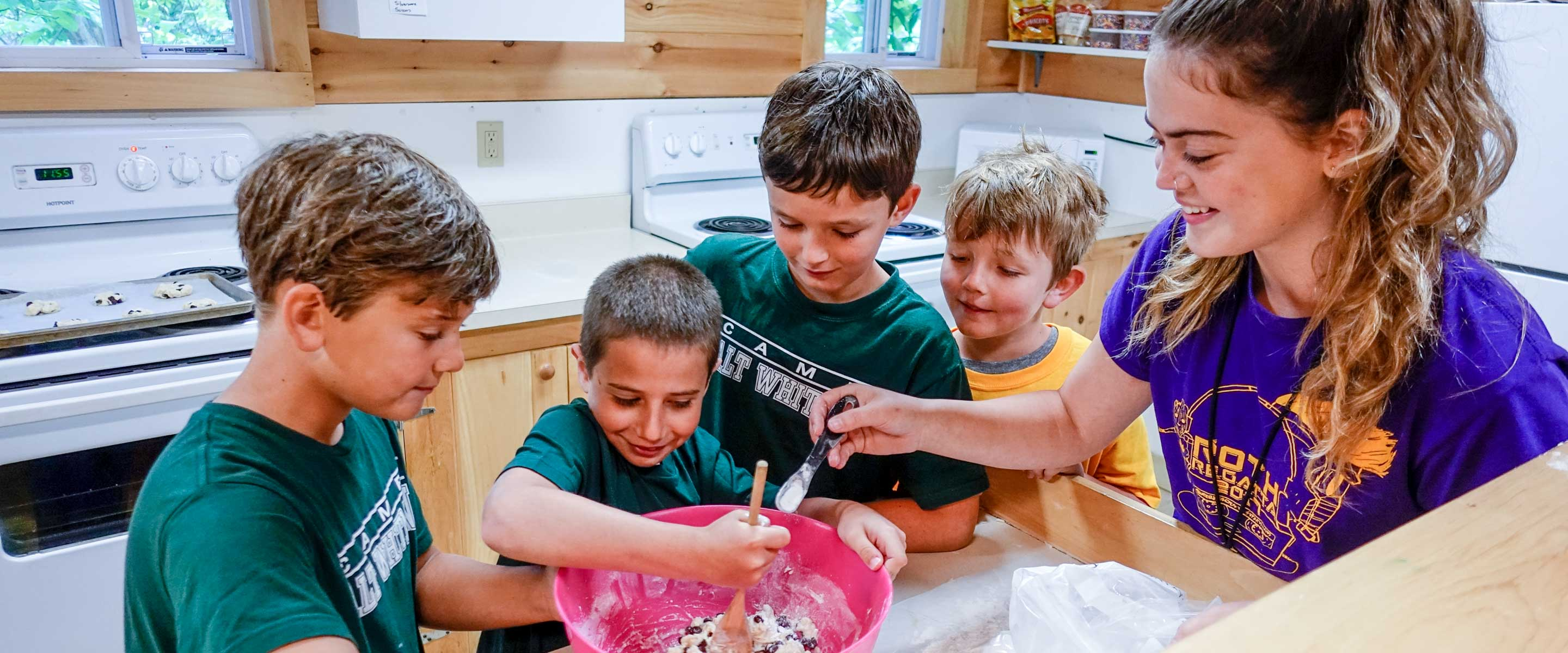 a group of boys mixing ingredients in a bowl with an instructor helping