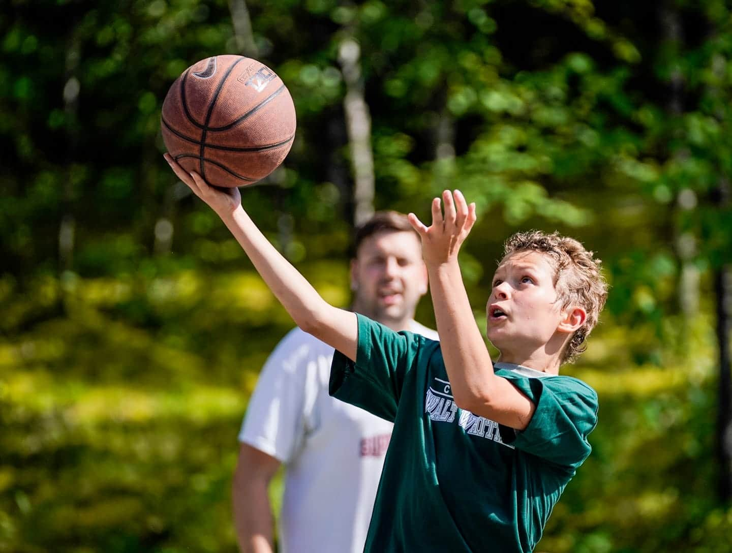 young camper doing a layup