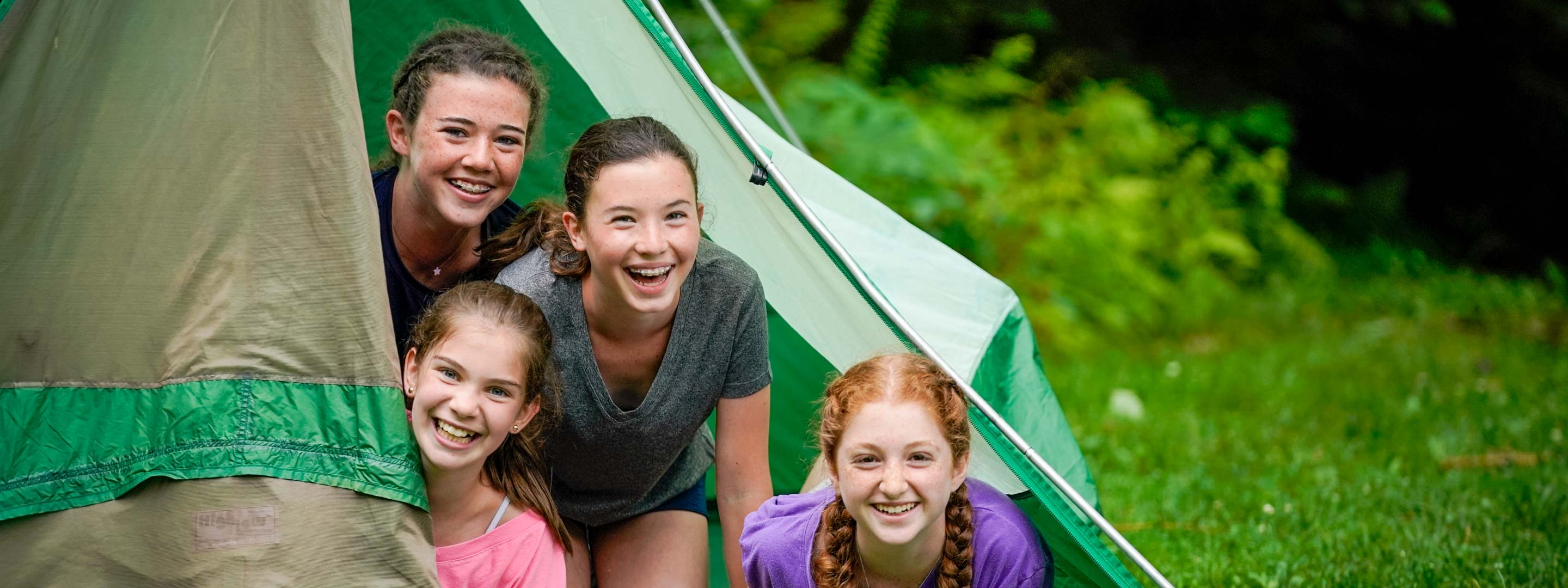 four young girls peaking out of a tent