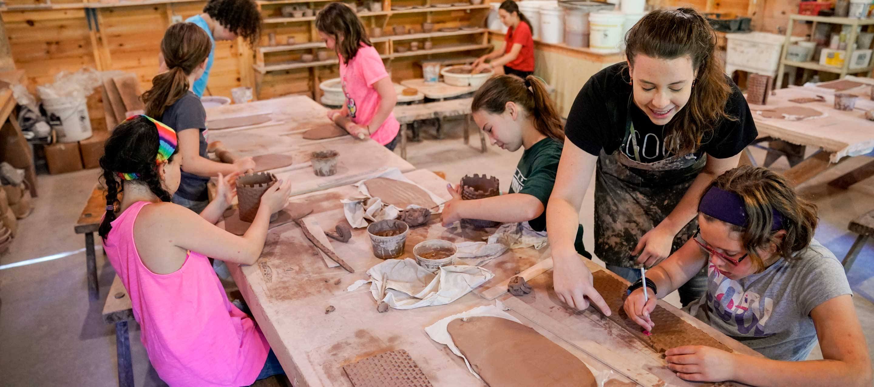 counselor helping a group of campers make ceramic creations