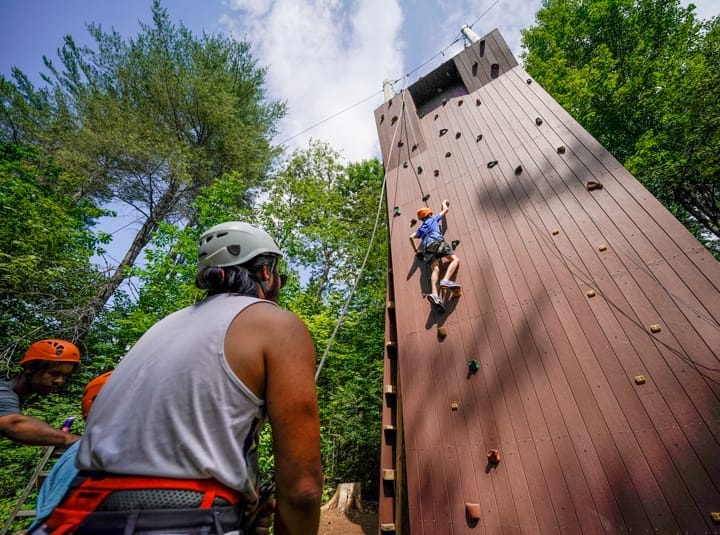 campers rock climbing while a counselor belays them