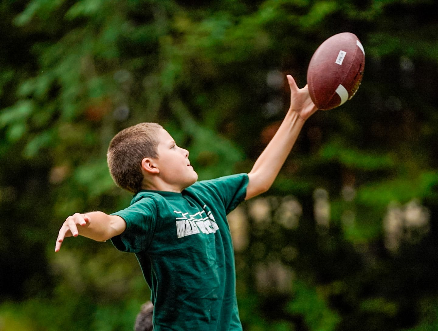 a young kid catching a football one handed