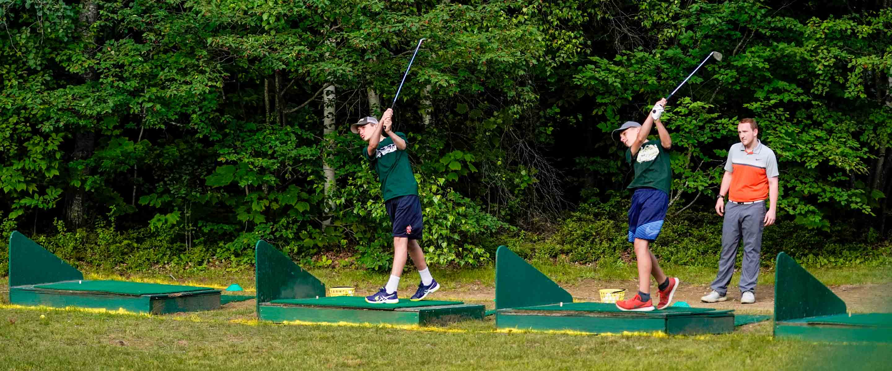 campers practicing their golf drives while an instructor watches