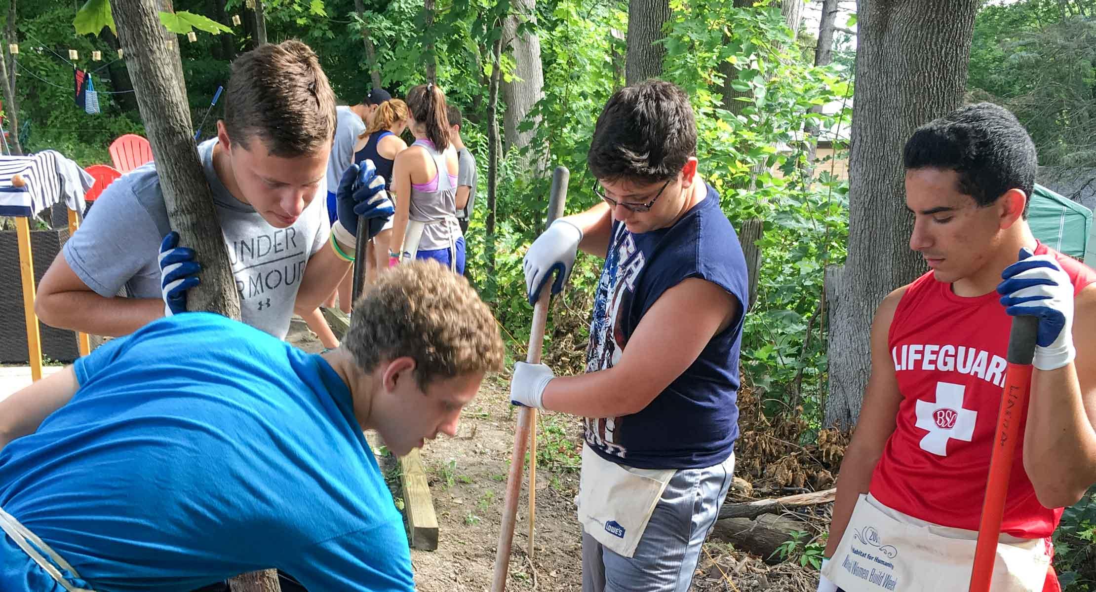 group of four young people planting a tree